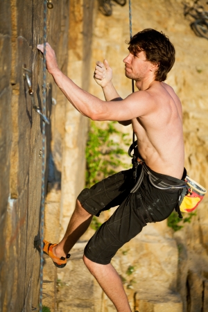 belay: young rock climber  climbs the cliff with a belay