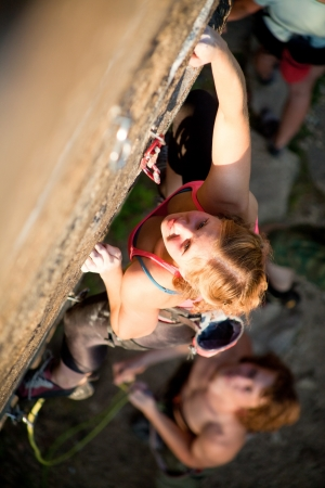 belay: Young red-haired girl climbs on a rock with a belay