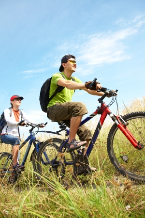 family bike: Couple of cyclists riding bicycles in countryside