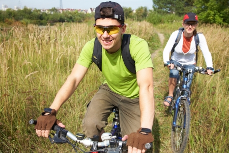 Couple of cyclists riding bicycles in countryside photo