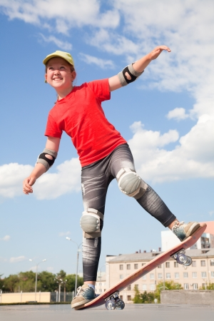 little sweet girl learns to ride  on  skateboard photo