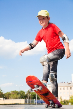little sweet girl  rides on  skateboard photo