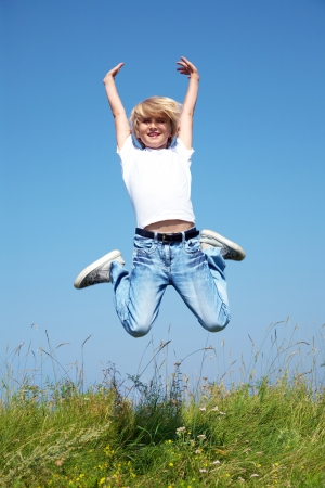 happy people jumping: Cute boy jumping on summer meadow against blue sky Stock Photo