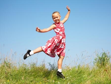 niños bailando: Linda chica saltando en el prado contra el cielo azul del verano