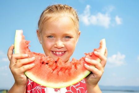Portrait of cute girl with peace of red watermelon on blue sky background photo