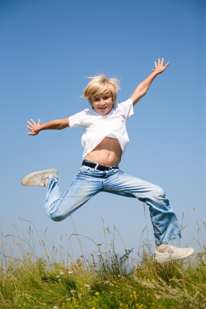 Cute boy jumping on summer meadow against blue sky photo