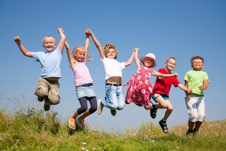 niños felices: Grupo de niños felices que saltan en prado del verano contra el cielo azul Foto de archivo