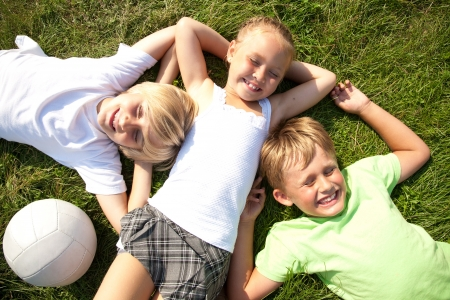 Tree cute children  lying in green grass and enjoying summertime photo
