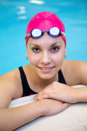 Portrait of a beautiful girl in a red cap at the swimming pool photo