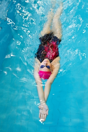 one adult: young woman swims on back in the pool