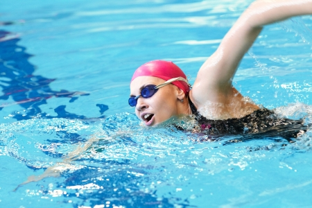 young girl swims freestyle in the pool photo