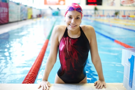 swimming race: Portrait of a beautiful girl in a red cap at the swimming pool
