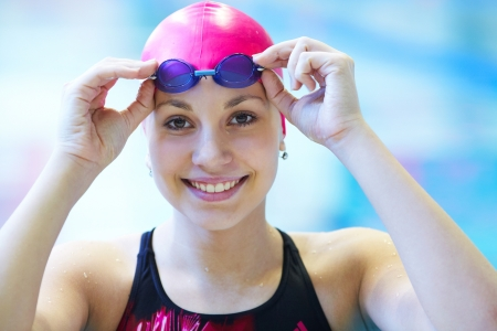 swimming competition: Portrait of a beautiful girl in a red cap at the swimming pool