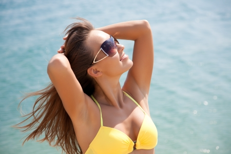 Portrait of young attractive woman having good time in the beach photo