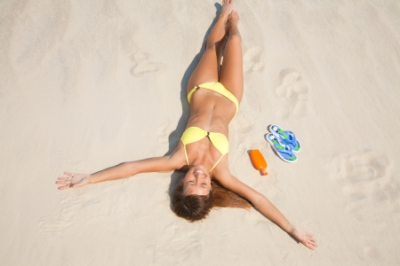 beautiful young woman in bikini lying and sunning on the beach under the bright sun photo