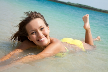 beautiful young woman in bikini lying  and smiling in sea at the resort photo