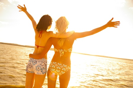 young girl bikini: two beautiful young girlfriends opened her hands with delight at the blue sea and sky Stock Photo