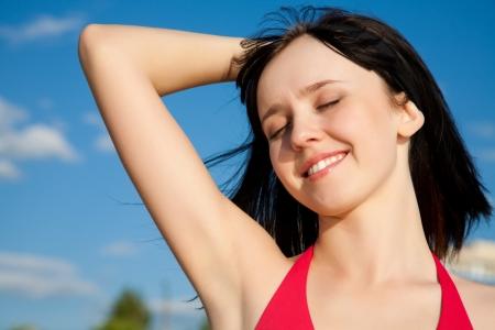 young girl in  bikini enjoying the sun closed her eyes photo