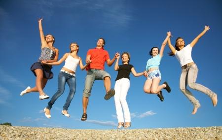 springende mensen: groep van gelukkige jonge mensen springen op het strand op mooie zomerse dag
