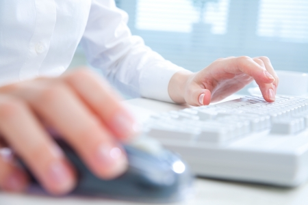 tecla enter: Detalle de las manos de una mujer usando una computadora en fondo de la oficina