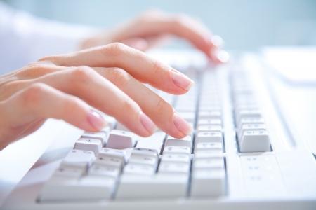 mecanografía: Mujeres manos escribiendo en el teclado de computadora blanco