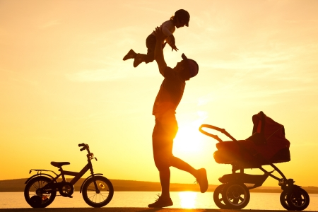 happy dad  daughter throws up into the sky next to the stroller at sunset photo