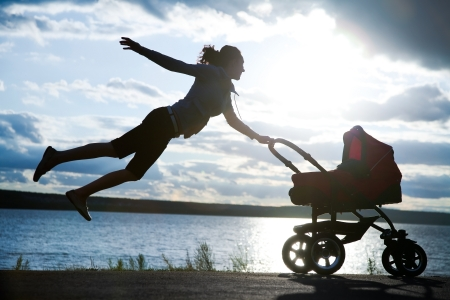 young mother is flying in stroller with a baby at sunset Stock Photo - 14348000