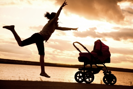 stroller: young mother is running to stroller with a baby at sunset