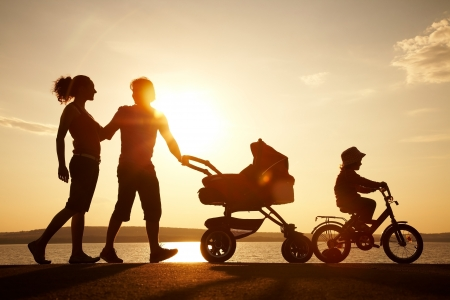 family exercise: Silhouettes of happy parents having good time with their little children on the seacoast Stock Photo