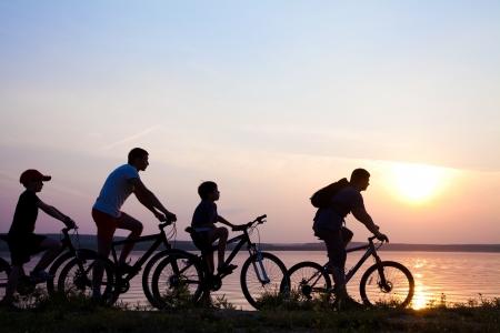 ciclista: de la familia en bicicleta admirando la puesta de sol en el lago. silueta