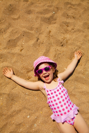 sonnenbaden: kleines Mädchen liegen auf einem Sandstrand und Sonnenbaden in der Sonne