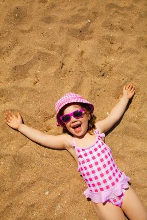 sunbath: little girl lying on a sandy beach and sunbathe in the sun