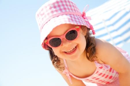little girl smiling fun in the hot beach under an umbrella