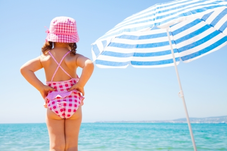 the little girl looks at the sea near a beach umbrella