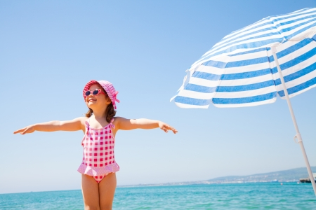 sun umbrellas: happy little girl at the seaside in the summer