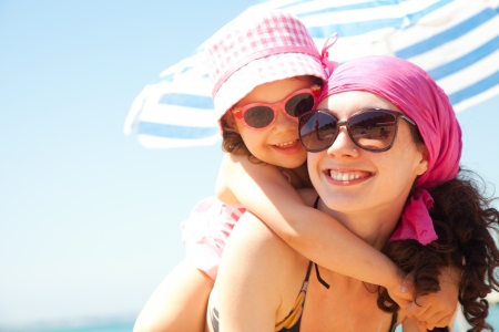 child swimsuit: little girl and her mother have  a good time at the seaside resort