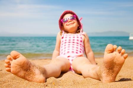 maillot de bain fille: petite fille couchée sur une plage de sable et se faire bronzer au soleil Banque d'images
