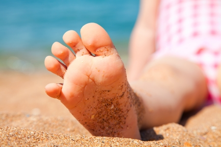 childs foot is close to the sandy beach of the seaside resort photo