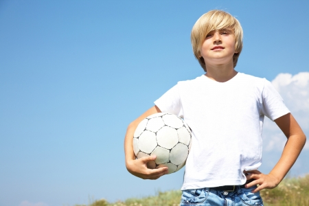 portrait of cute teen boys with soccer ball against the blue sky photo