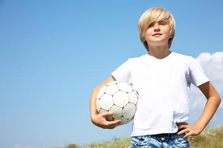 futbol infantil: retrato de lindos los chicos adolescentes con el balón de fútbol contra el cielo azul