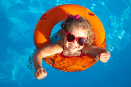 pool fun: Funny little girl swims in a pool in an orange life preserver