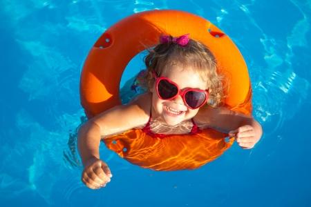 Lustige kleine M�dchen schwimmt in einem Pool in einem orangefarbenen Rettungsring Lizenzfreie Bilder