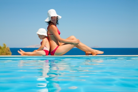 Young mother with baby daughter sitting on the edge of the pool and stare at the sea