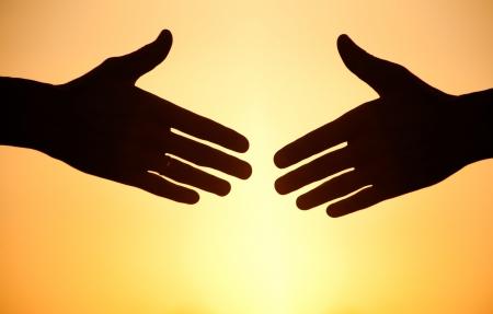 twee armen uitstrekt naar elkaar te schudden tegen de zonsondergang