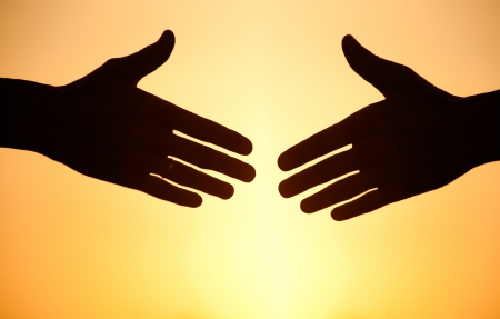 black handshake: two arms stretching towards each other to shake against the sunset