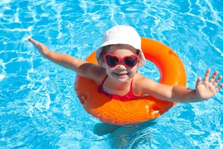 Grappig meisje zwemt in een zwembad in een oranje reddingsvest Stockfoto