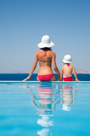 tourist resort: Young mother with baby daughter sitting on the edge of the pool and stare at the sea