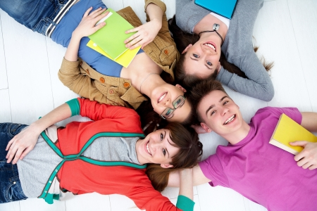secondary schools: group of teenage friends look up at the camera with bright smiles