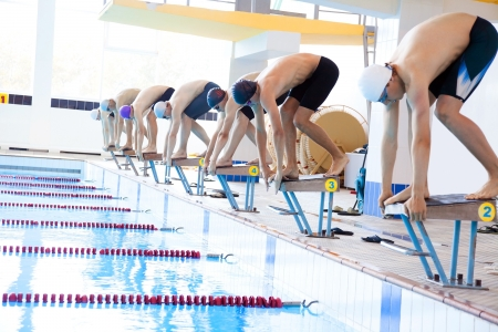 were: Boys swimmers were bent on starting pedestals in the pool