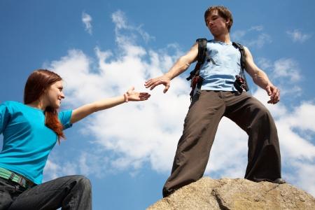 caminante llega a la mano a la mujer en la parte superior de montaña Foto de archivo